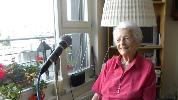 Alice Marti in ihrem Zimmer im Altersheim Lyss. Sie sitzt an einem Holztisch mit Spitzendecke. Ein grosses Mikrofon ist vor ihr aufgebaut.