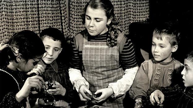 Historische Fotografie mit ein paar Kindern, die Weihnachtskugeln in der Hand halten.