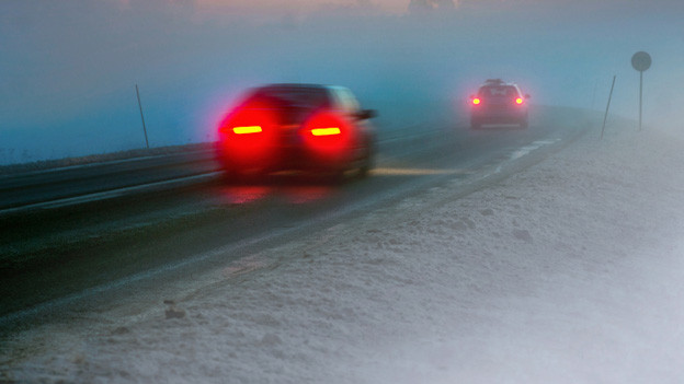 Verschwommenes Bild von zwei Fahrzeugen, die im Schneegestöber unterwegs sind.