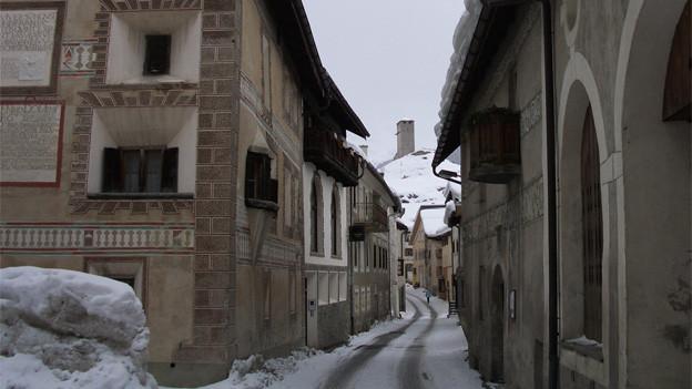 Zwei typische Bündner Häuser links und rechts von einer Gasse in Ardez.