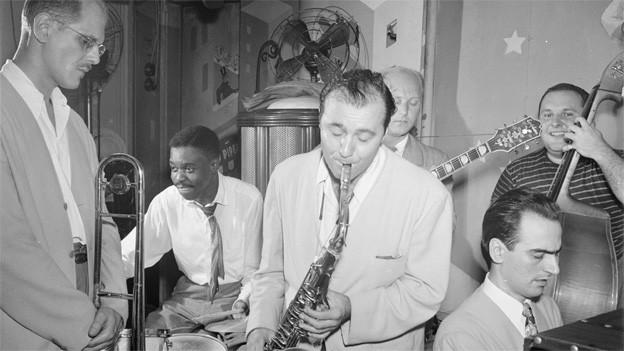 Schwarz-Weiss Fotografie mit sechs Musikern, die Trompete, Schlagzeug, Saxophon, Gitarre, Kontrabass und Klavier spielen.