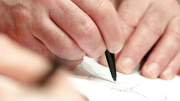 Eine Hand, die mit einem Kugelschreiber zur Unterschrift ansetzt.