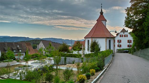 Blick auf das Dorf mit Kirche und Gemeindehaus.