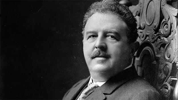 Schwarz-Weiss-Fotografie des Komponisten, der in einem dunklen Anzug in einem Sessel sitzt.