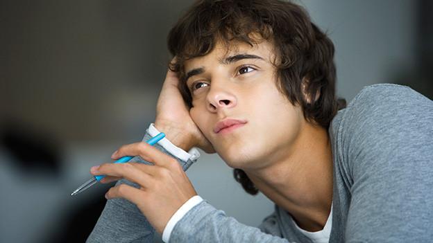 Ein junger Mann träumt mit einem Schreiber in der Hand vor sich hin.