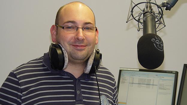 Der Moderator trägt seine Kopfhörer um den Hals und steht im Studio vor einem Mikrofon.