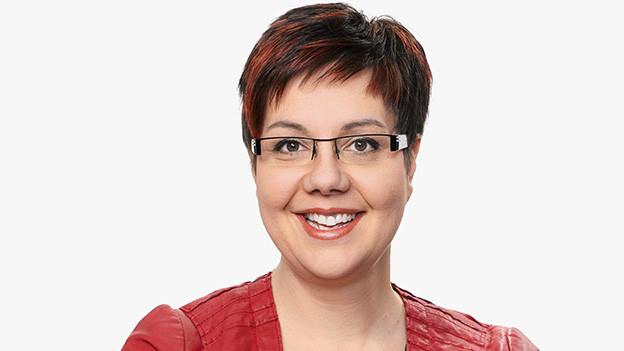 Die dunkelhaarige Moderatorin trägt eine Brille und eine dunkelrote Lederjacke.