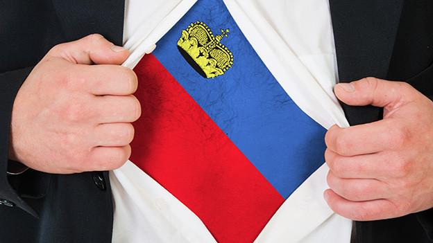 Ein Mann reisst sein weisses Hemd auf, darunter trägt er ein Shirt mit Liechtensteiner Wappen.