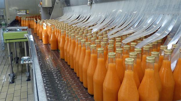 Mit Rüeblisaft gefüllte Flaschen auf einem Fliessband.