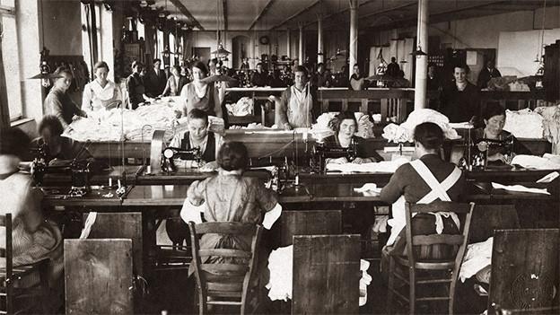 Historische Fotografie mit einem Raum voll Näherinnen an ihren Nähmaschinen.