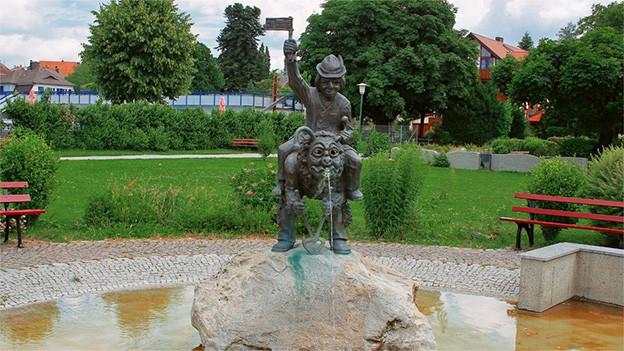Zwei Narrenfiguren auf einem Stein in einem Brunnen.