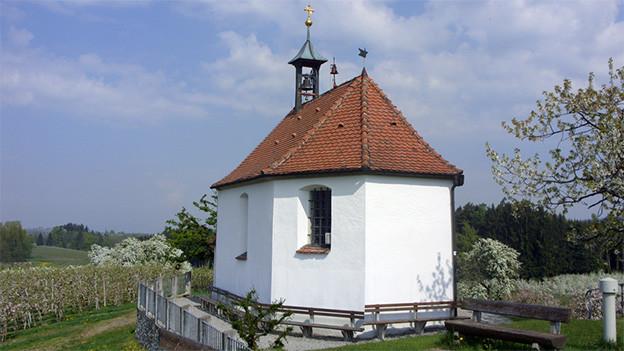 Eine kleine weisse Kapelle in einer sommerlichen Landschaft.