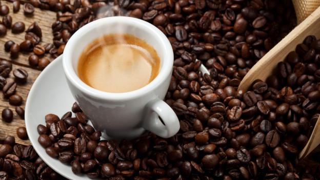 Heisse Tasse Kaffee inmitten von gerösteten Kaffeebohnen