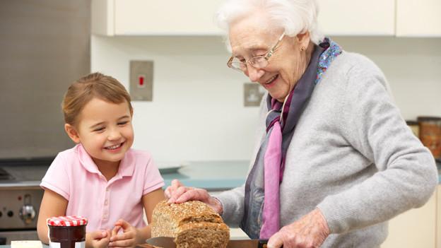 Ein kleines Mädchen sitzt fröhlich am Tisch, während seine Grossmutter mit einem grossen Messer Brot schneidet.