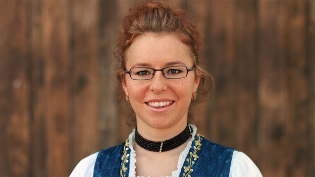 Nadja Räss mit hochgesteckter Frisur, Brille und in einer Tracht.