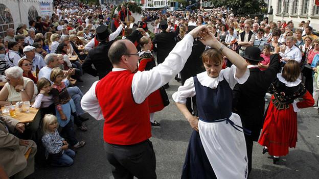 Viele Zuschauer säumen die Tanzfläche, auf der mehrere Paare in Trachten am Tanzen sind.