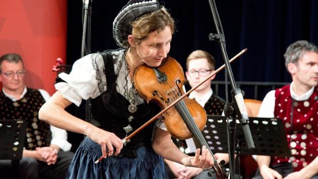 Geigenspielerin in volkstümlicher Tracht beim Spiel während Aufzeichnung.