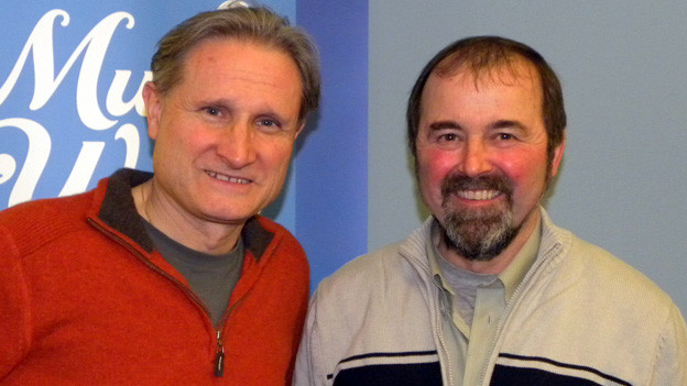 Moderator und Interviewgast posieren vor dem Logo von SRF Musikwelle.