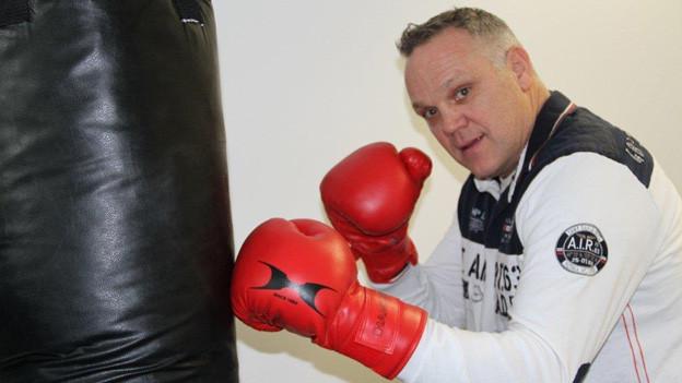 René Schmid trägt einen Trainingsanzug und rote Boxhandschuhe und steht zum Angriff bereit vor einem schwarzen Sandsack.
