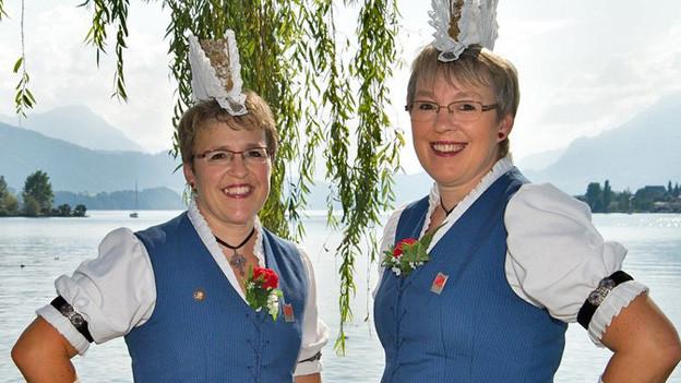 Kiser-Hodel vor See mit Trachten und dazugehörigen Hüten.