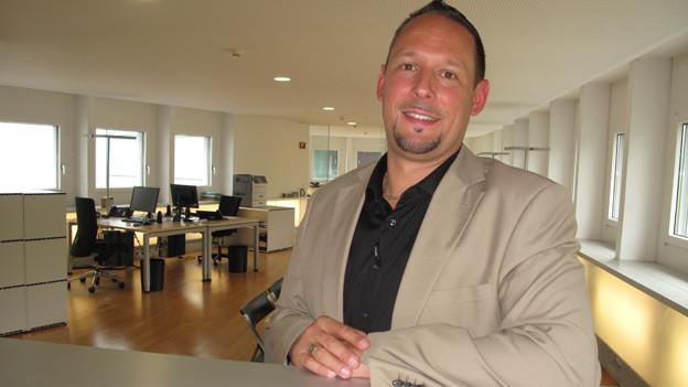 Stefan Fischer trägt eine beige Weste über einem schwarzen Hemd und lehnt sich an eine Bürotheke.