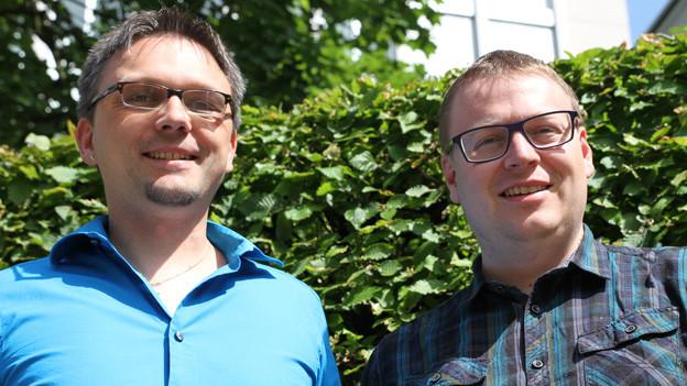 Schnappschuss mit Interviewgast und Moderator vor einer grünen Hecke an einem sonnigen Tag.