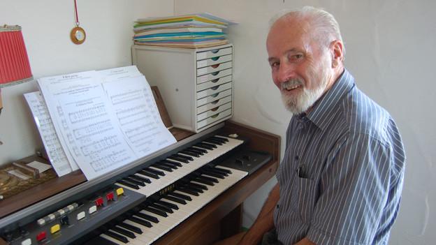 Der 76-jährige Mann sitzt in seinem Wohnzimmer am Klavier.