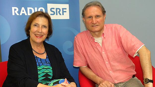 Interviewpartnerin und Moderator sitzen in roten Sesseln vor dem blau-weissen Logo von SRF Musikwelle.