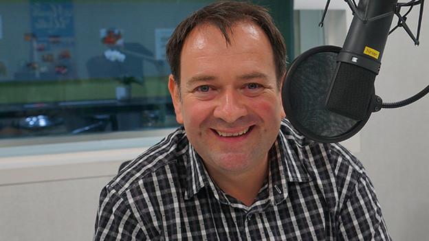 Thomas von Arx trägt ein kariertes Hemd und sitzt vom dem Mikrofon im Aufnahmestudio.