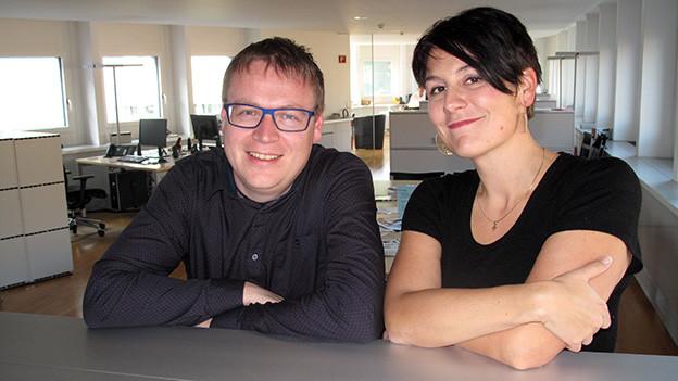 Moderator und Gast stützen sich mit ihren Armen auf einem Büromöbel ab.