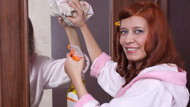 Frau in rosa Bademantel putzt Spiegelschranktüre mit Wasser und Lappen.