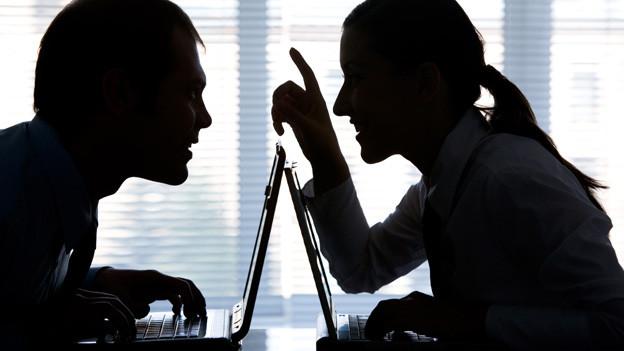 Schattenbild von einem Mann und einer Frau, die sich über ihre Laptops hinweg unterhalten.
