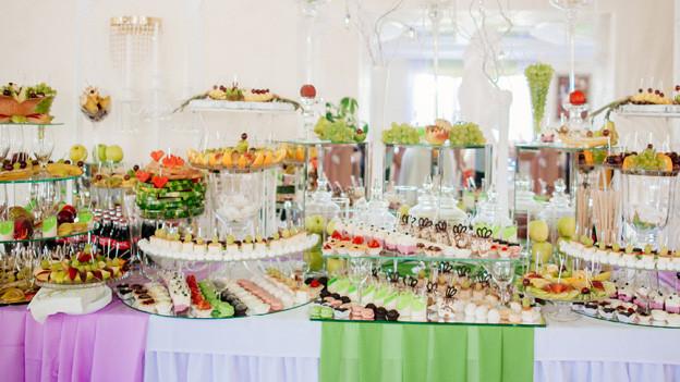 sehr viele verschiedene Nachspeisen dicht angeordnet auf einem mit farbigen Tüchern dekorierten Tisch.