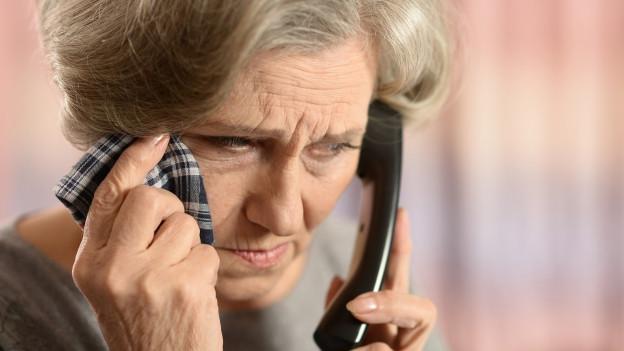 Eine Frau tupft sich während dem Telefonieren mit dem Taschentuch den Schweiss von der Stirn.