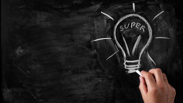 Eine Hand zeichnet mit weisser Kreide eine Glühbirne mit dem Wort «Super» auf eine Wandtafel.