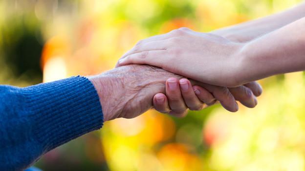 Eine junge Hand legt sich mitfühlend auf die Hand einer älteren Person.