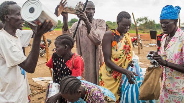 Sudanesische Flüchtlinge in ärmlicher Kleidung.