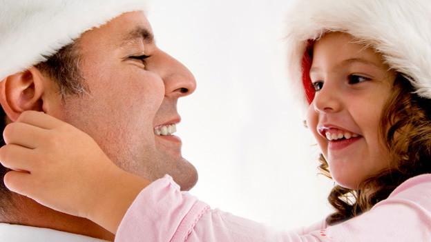 Ein lachendes Mädchen zieht seinen Vater lachend am Ohr.