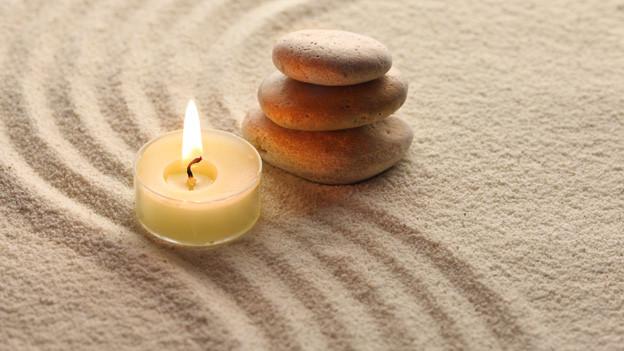 Eine Kerze steht neben ein paar aufgeschichteten Steinen im Sand.