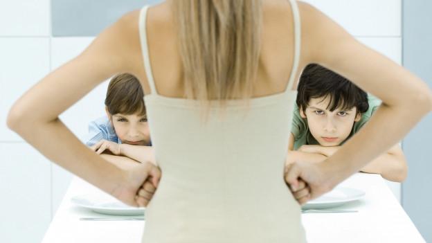 Mutter verschränkt die Arme in der Hüfte und schimpft Kinder aus.