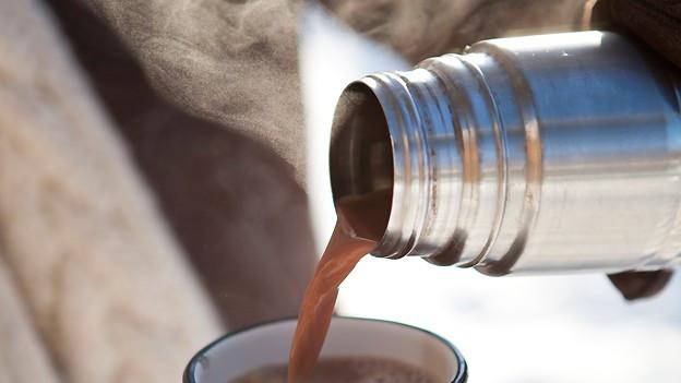 Kaffe wird von Thermoskanne in Tasse gegossen.