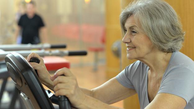 Eine ältere Dame sitzt im Fitnessraum auf einem Fahrrad.