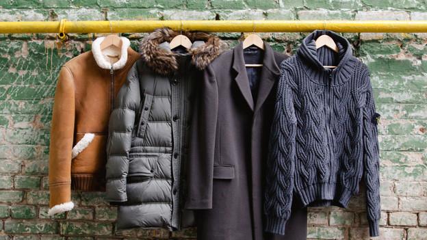 Drei Winterjacken und ein Wintermantel hängen an einem Kleiderbügel an einer gelben Stange, die an einer Hausmauer befestigt ist.