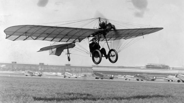 Auf der Schwarz-Weiss Fotografie hängt der Pilot zwischen Flügen und Fahrgestell.