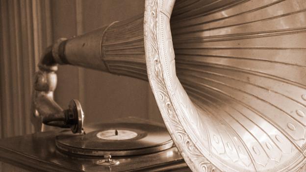 Altes Grammophon mit einem grossen Trichter als Lautsprecher auf einer alt wirkenden Fotografie.