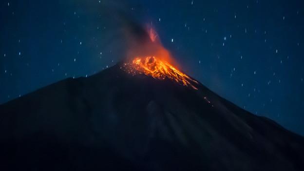 Geringer Ausbruch eines Vulkans unter dem Nachthimmel.