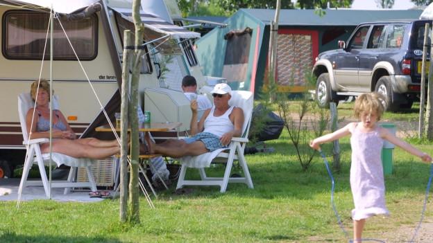 Mutter und Vater sitzen vor ihrem Wohnwagen, Kind hüpft mit ihrem Springseil.