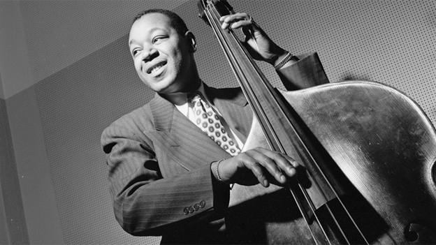 Schwarz-Weiss Fotografie des Musikers, der in Schale und Krawatte die Basssaiten zupft.