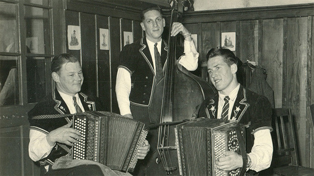 Die Schwarz-Weiss Fotografie zeigt die drei Musiker in einer Gaststube.