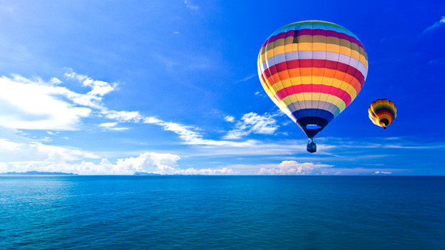 Zwei farbig gestreifte Heissluftballons über dem offenen Meer.